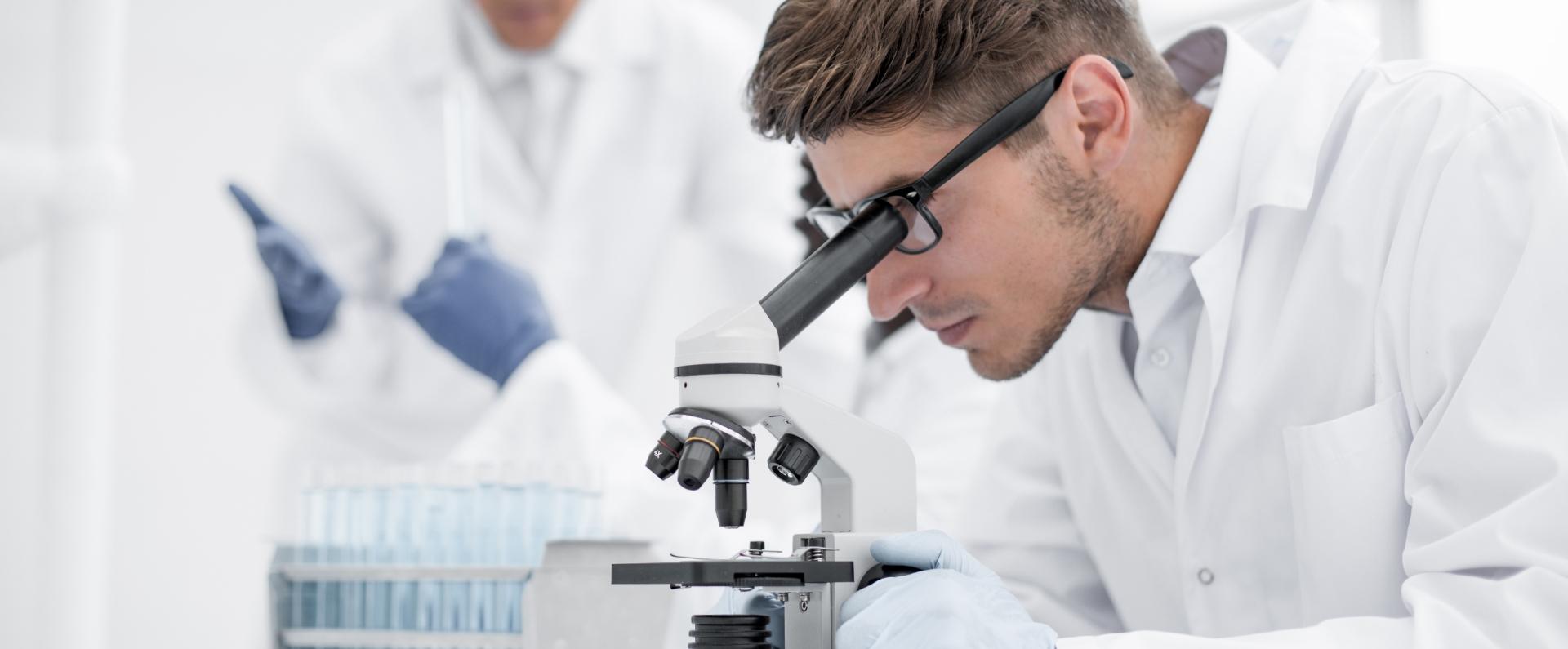 Eine junge Person guckt durch ein Mikroskop