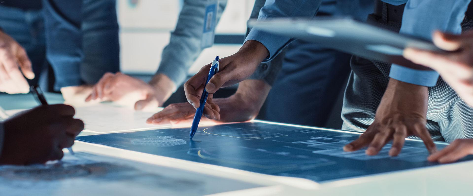 Teamplanung, jemand hält einen Stift auf eine Blaupause
