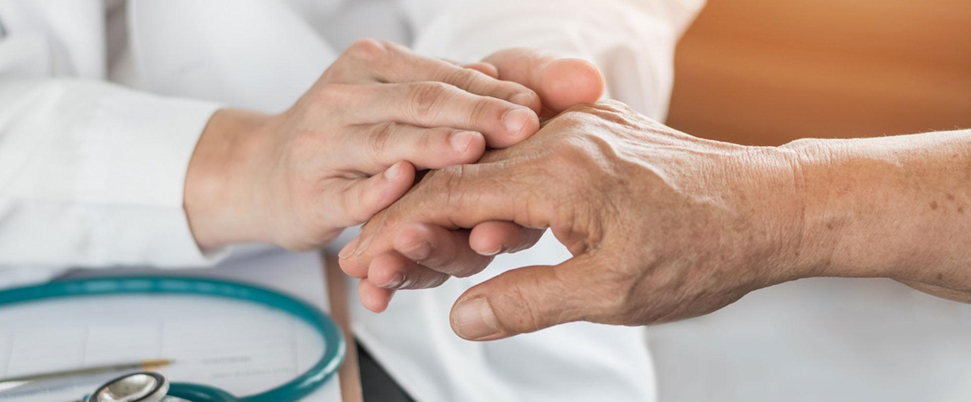 Eine junge Person hält die Hand einer älteren Person